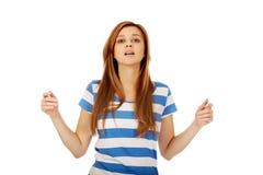 Mujer adolescente con los brazos extendidos que miran para arriba Fotografía de archivo libre de regalías