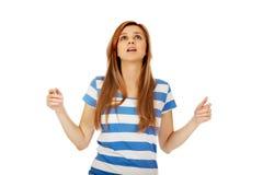 Mujer adolescente con los brazos extendidos que miran para arriba Imagen de archivo libre de regalías