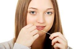 Mujer adolescente con seda dental Imágenes de archivo libres de regalías
