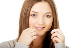 Mujer adolescente con seda dental Imagenes de archivo