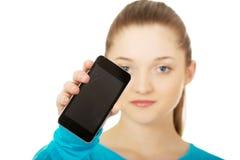 Mujer adolescente con un teléfono celular quebrado Imagen de archivo