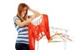 Mujer adolescente confusa con nada vestirse Fotografía de archivo