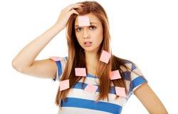 Mujer adolescente cubierta con las notas de post-it Foto de archivo