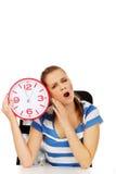 Mujer adolescente de bostezo cansada que sostiene el reloj Imágenes de archivo libres de regalías