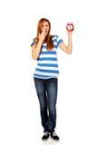 Mujer adolescente de bostezo que sostiene el despertador Foto de archivo