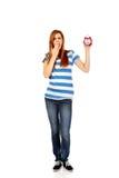 Mujer adolescente de bostezo que sostiene el despertador Imagen de archivo