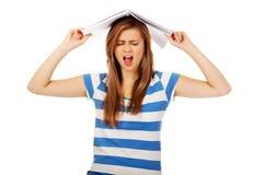 Mujer adolescente de griterío con el cuaderno en la cabeza Imagen de archivo