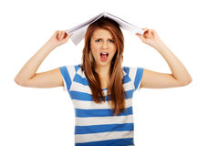 Mujer adolescente de griterío con el cuaderno en la cabeza Fotos de archivo
