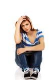 Mujer adolescente de la depresión que se sienta en el piso Imagenes de archivo