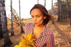 Mujer adolescente de la muchacha que sostiene el ramo de hojas de otoño Fotos de archivo libres de regalías