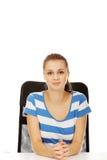 Mujer adolescente de la sonrisa que se sienta en el escritorio Imagen de archivo libre de regalías