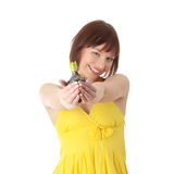 Mujer adolescente en la alineada amarilla que sostiene la pequeña planta Fotografía de archivo