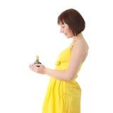 Mujer adolescente en la alineada amarilla que sostiene la pequeña planta Foto de archivo libre de regalías
