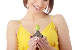 Mujer adolescente en la alineada amarilla que sostiene la planta smal Imagen de archivo