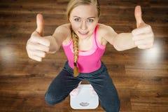 Mujer adolescente en la máquina de la báscula de baño Foto de archivo libre de regalías