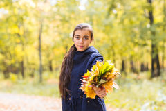 Mujer adolescente feliz hermosa joven de la muchacha que sostiene el ramo de hojas de otoño y que sonríe, en el fondo del bosque Fotos de archivo