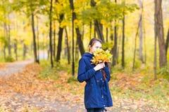 Mujer adolescente feliz hermosa joven de la muchacha que sostiene el ramo de hojas de otoño y que sonríe, en el fondo del bosque Foto de archivo