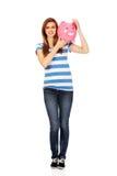 Mujer adolescente feliz que lleva a cabo el piggybank Imagen de archivo