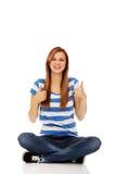 Mujer adolescente feliz que se sienta con legged cruzado Imagen de archivo libre de regalías