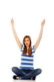 Mujer adolescente feliz que se sienta con los brazos para arriba Fotos de archivo