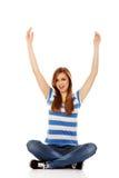 Mujer adolescente feliz que se sienta con los brazos para arriba Imagenes de archivo