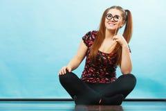 Mujer adolescente feliz que sostiene las lentes falsas en el palillo Imágenes de archivo libres de regalías