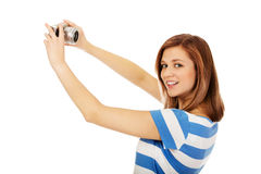 Mujer adolescente feliz que toma el selfie con la cámara clásica del slr Fotografía de archivo libre de regalías