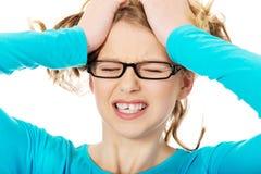Mujer adolescente frustrada que tira de su pelo Imagen de archivo libre de regalías