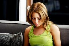 Mujer adolescente infeliz en el sofá Fotos de archivo libres de regalías