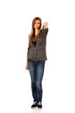 Mujer adolescente infeliz joven que muestra el pulgar abajo Imagen de archivo libre de regalías
