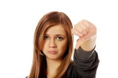Mujer adolescente infeliz joven que muestra el pulgar abajo Fotografía de archivo libre de regalías