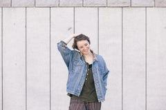 Mujer adolescente joven alegre que se coloca en la calle con el hapiness a Fotografía de archivo