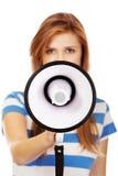Mujer adolescente joven de griterío con el megáfono Imagenes de archivo