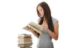 Mujer adolescente joven del estudiante que lee un libro Imágenes de archivo libres de regalías