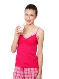 Mujer adolescente joven en leche de consumo del pijama rosado Foto de archivo libre de regalías