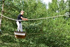 Mujer adolescente joven en una aventura del parque de la cuerda de la copa Foto de archivo