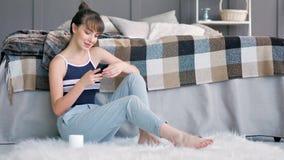 Mujer adolescente joven hermosa que usa el smartphone que se sienta en la alfombra mullida en dormitorio almacen de video