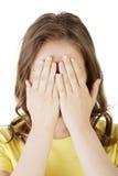 Mujer adolescente joven que cubre su cara con las manos Imagen de archivo libre de regalías