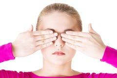 Mujer adolescente joven que cubre su cara con las manos Fotos de archivo