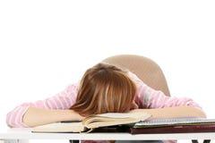 Mujer adolescente joven que duerme en el escritorio Fotos de archivo libres de regalías