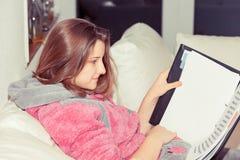 Mujer adolescente joven que estudia en casa imagen de archivo libre de regalías