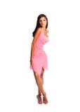 Mujer adolescente joven que lleva una presentación rosada del vestido aislada en un fondo blanco Foto de archivo
