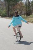 Mujer adolescente joven que monta abajo de una calle residencial de la vecindad que equilibra en un Unicycle Imágenes de archivo libres de regalías