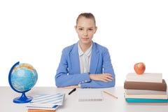 Mujer adolescente joven que se sienta detrás del escritorio aislado Foto de archivo libre de regalías