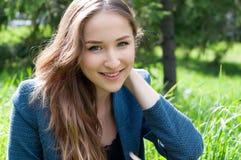 Mujer adolescente joven que se sienta en la hierba en parque Imagen de archivo