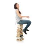 Mujer adolescente joven que se sienta en los libros Fotos de archivo