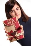 Mujer adolescente joven que soporta una tarjeta del amor Imagenes de archivo