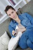 Mujer adolescente joven que ve la TV en el sofá Foto de archivo libre de regalías
