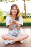 Mujer adolescente joven y smartphone a disposición que sonríen con emoti feliz Imagenes de archivo