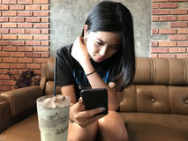 Mujer adolescente linda asiática que juega el teléfono elegante Fotografía de archivo